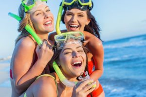 Three young women wearing snorkeling gear.
