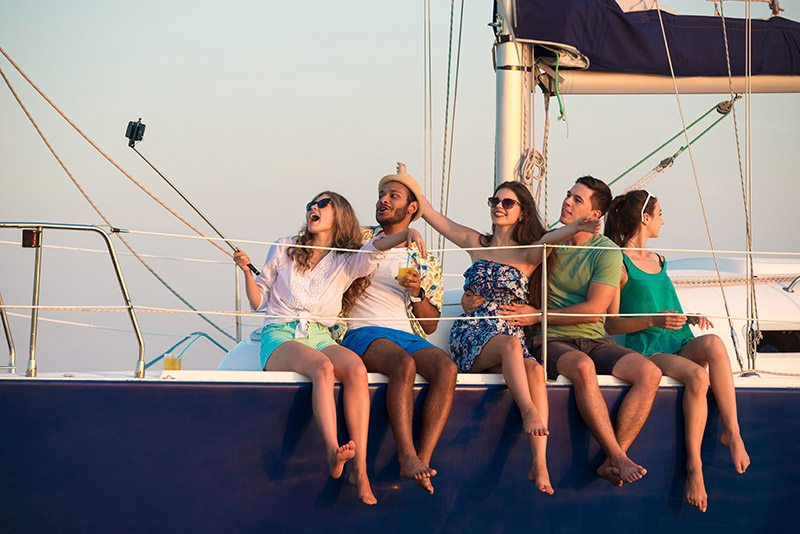 Five young people sitting on edge of sailboat.