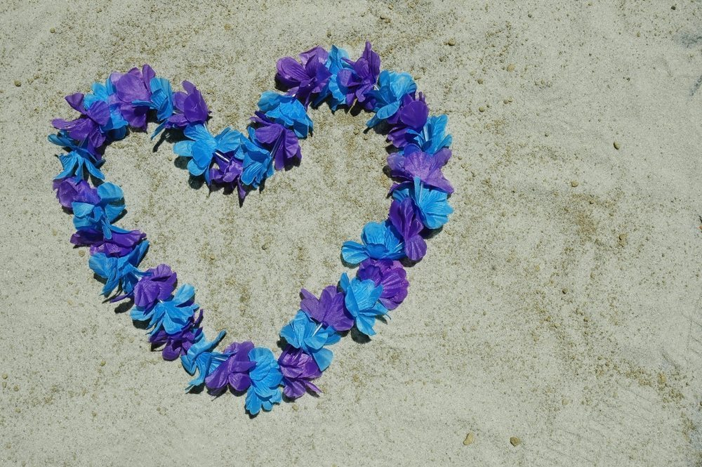 Flower leis made of blue and purple flowers in shape of heart on beach.
